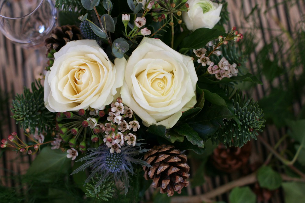 winter table arrangement with ivory roses, pine cones, thistles , waxflower and eucalyptus