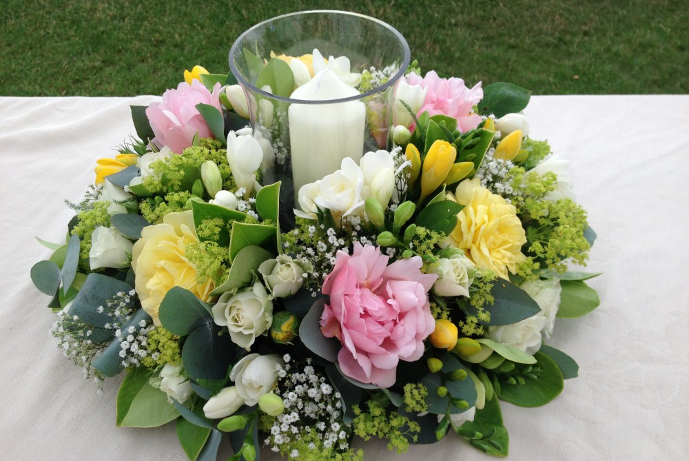 table centre arrangement with hurricane lamp for a summer dinner party