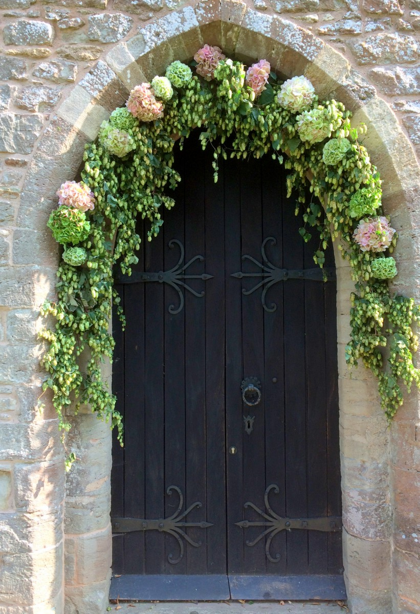 Hop and hydrangea archway wedding flowers at St Bartholomews church Homme House