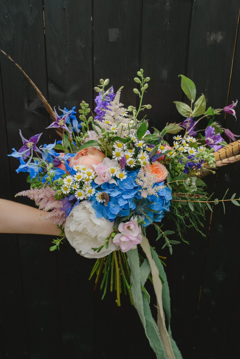 boho brides bouquet with peonies and feathers