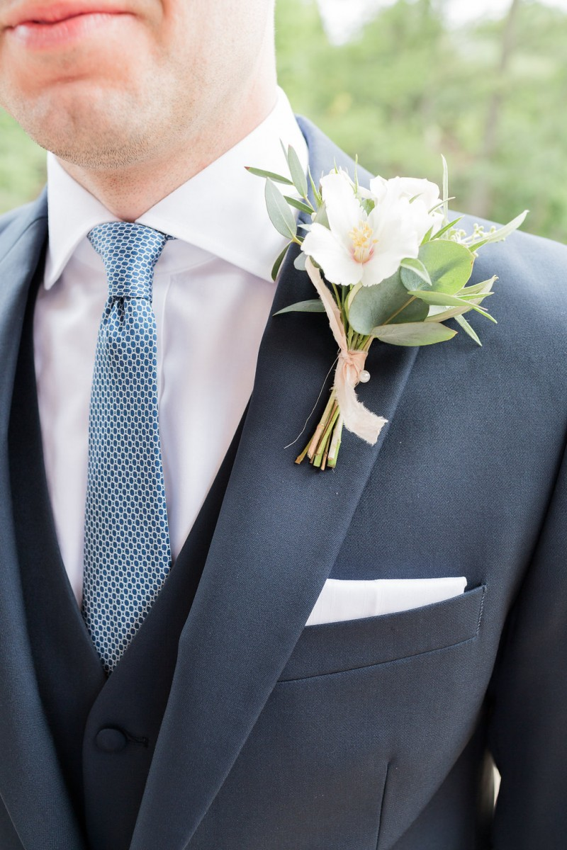 Grooms buttonhole with mock orange, a rose and foliage