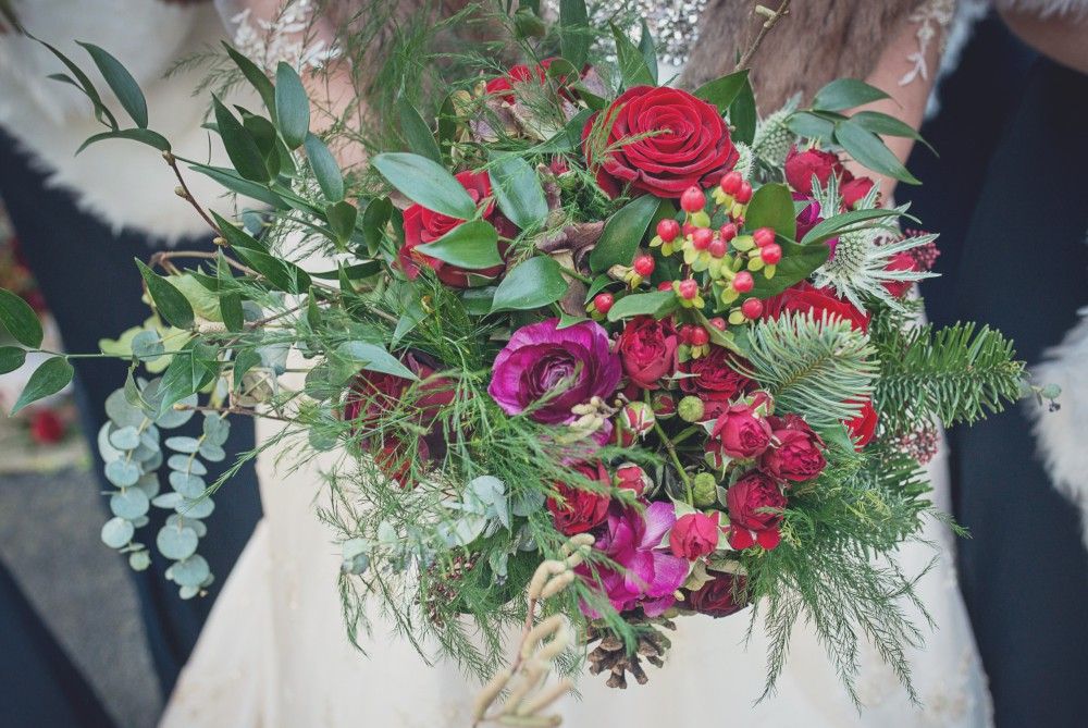 red and green winter wedding brides bouquet